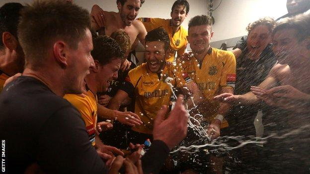 Maidstone United players celebrate in the changing room after the game