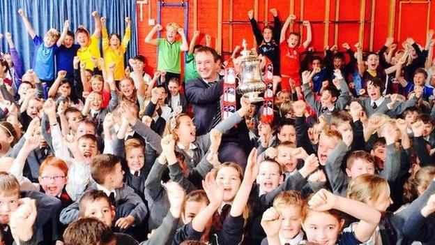 The FA Cup being help up and surrounded by happy children