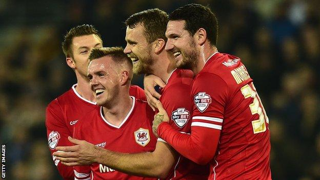 Cardiff players celebrate after Reading player Alex Pearce's own goal