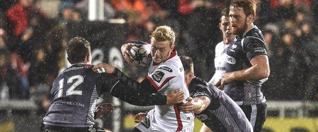 Ospreys tacklers halt the run of Ulster full-back Stuart Olding in the Belfast rain
