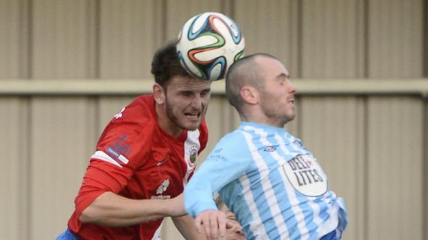 Linfield's Jamie Richards and Warrenpoint Town's Stephen Hughes in aerial action at Milltown
