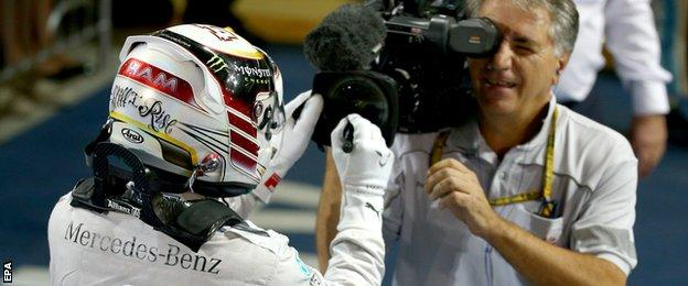 Lewis Hamilton signs the lens after winning the 2014 Drivers Championship