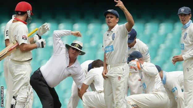 Phil Hughes is attended to after being hit by the ball. 25 Nov 2014