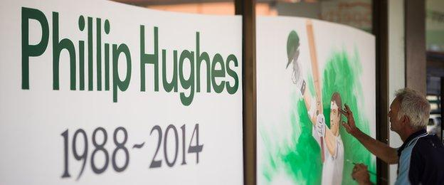 A portrait is painted on a store display in memory of Australian cricketer Phillip Hughes.
