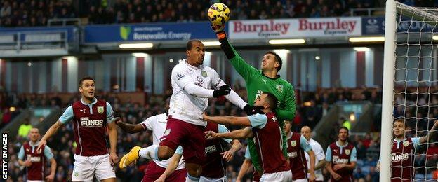 Burnley keeper Tom Heaton punches the ball away from Villa's Gabriel Agbonlahor