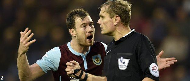 Ashley Barnes argues with referee Graham Scott