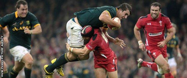 Wales's Leigh Halfpenny tackles Eben Etzebeth of South Africa