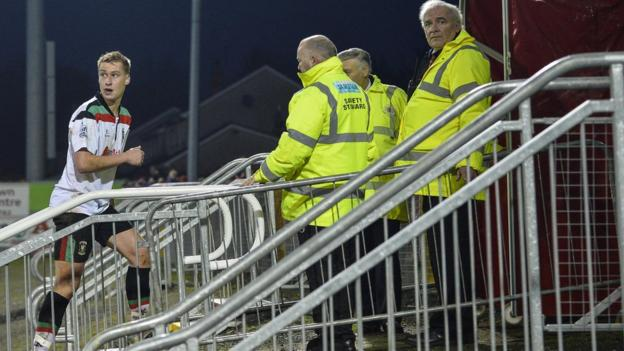 Glentoran defender Calum Birney makes his way off the pitch after being shown a second yellow card for a hand-ball offence at Portadown