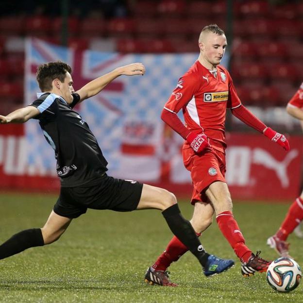 Ballymena United midfielder Mark Surgenor stretches to challenge Jude Winchester of Cliftonville