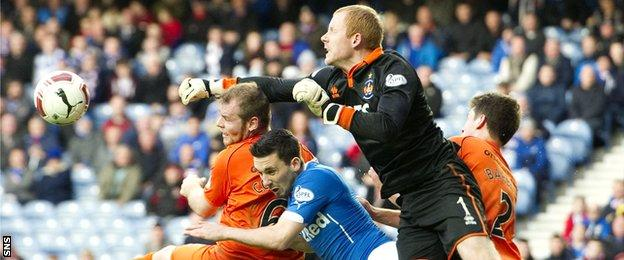 Rangers sub Nicky Clark is outnumbered as Craig Samson punches the ball clear
