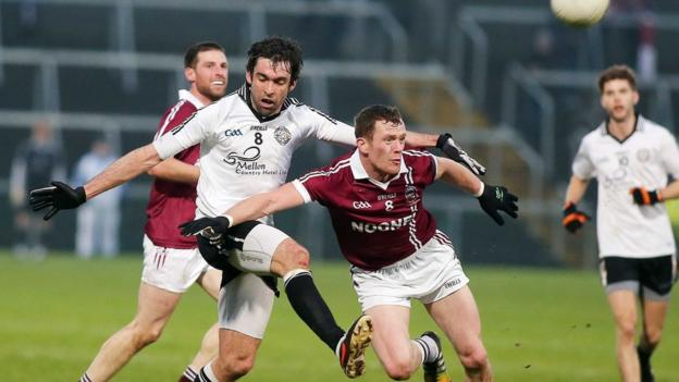 Joe McMahon of Omagh comes under pressure from Slaughtneil's Patsy Bradley