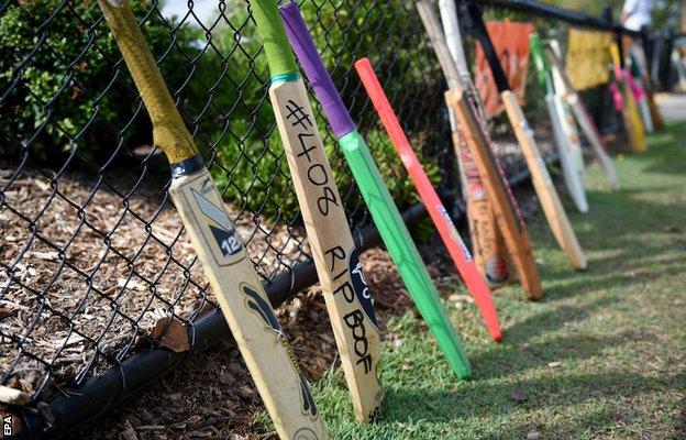 Cricket bats lean against the front fence of St Patrick's Primary School as a tribute to former student Hughes