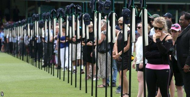 Mourners gather for a memorial service at the Sydney Cricket Ground and look at 63 bats with inscriptions detailing the career of Phillip Hughes