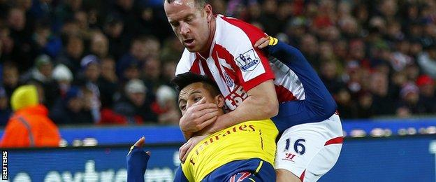 Charlie Adam wrestles Alexis Sanchez for the ball