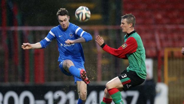 Ballinamallard's Colin McLaughlin passes the ball as Glentoran's Marcus Kane prepares to challenge