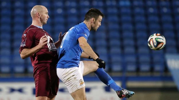 Institute captain Paddy McLaughlin keeps tabs on Glenavon forward Eoin Bradley during the 1-1 draw