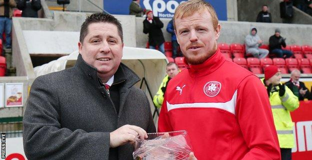 Cliftonville chairman Gerard Lawlor makes a presentation to skipper Gorge McMullan who was making his 500th appearance for the north Belfast club