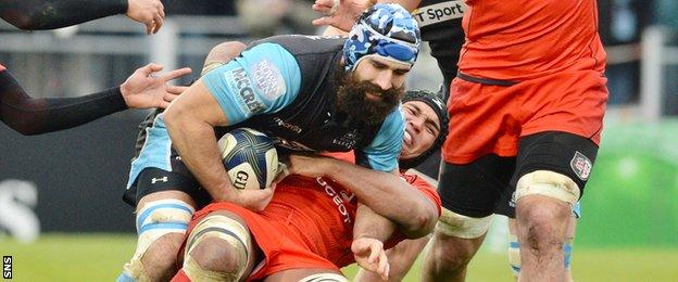 Glasgow captain Josh Strauss is tackeld by Toulouse skipper Thierry Dusautoir