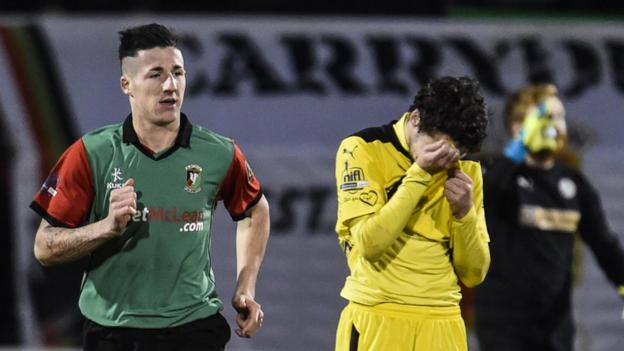 Danny McKee runs back to the centre circle after scoring Glentoran's late winner while Cliftonville's Tomas Cosgrove shows his disappointment