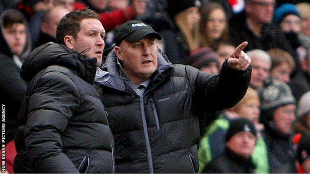 Russell Slade discusses tactics with assistant manager Scott Young
