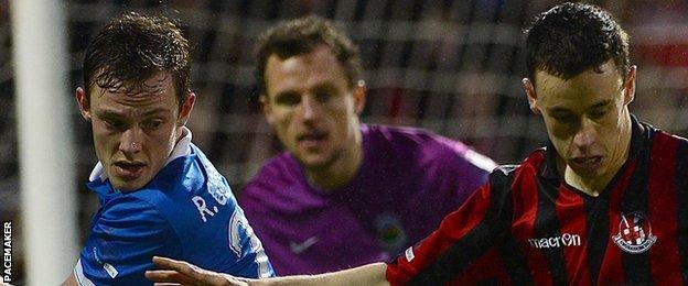 Linfield defender Reece Glendinning in action against Paul Heatley of Crusaders