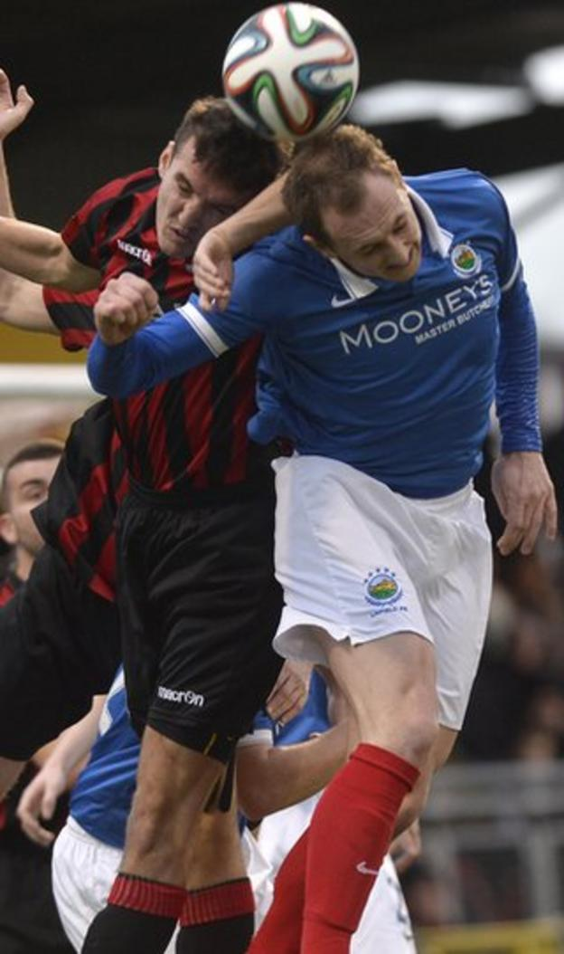 Josh Robinson and Linfield midfielder Sammy Morrow battle for the high ball in the 2-1 win for Crusaders which leaves them just a point behind the Blues