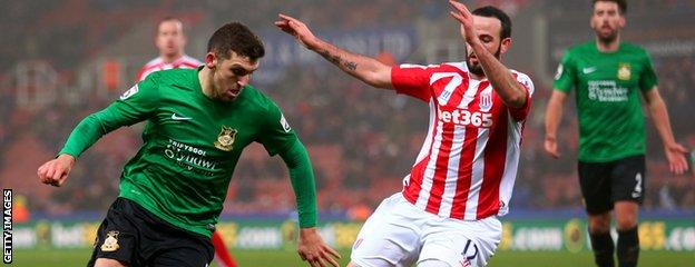 James Pearson of Wrexham runs with the ball under pressure from Marc Wilson of Stoke City during the FA Cup Third Round match