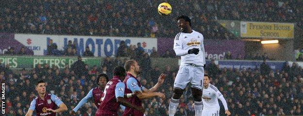 Wilfired Bony of Swansea City heads the ball towards goal against Aston Villa