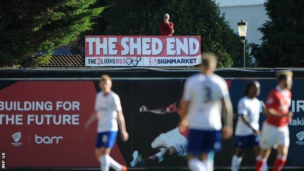 Bristol City fan Ben Swift watches a game from his shed roof