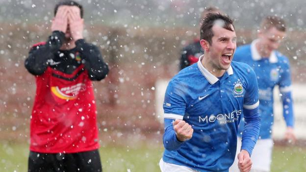 Andrew Waterworth celebrates in the snow after he scores his second goal in Linfield's 2-0 win over Championship side Tobermore United