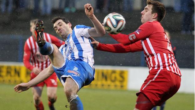 Coleraine midfielder Michael Hegarty and Warrenpoint Town forward Ruairi Devlin battle for the ball at the Showgrounds