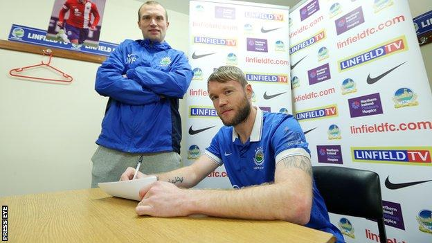 Grant McCann signs on the dotted line for Linfield with manager Warren Feeney looking on
