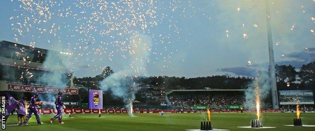 Tim Paine and Ben Dunk of the Hurricanes walk through fireworks out to the middle to open the innings during the Big Bash League match between the Hobart Hurricanes and the Brisbane Heat at Blundstone Arena