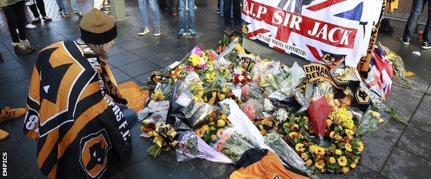 A Wolves fan lays a tribute to Sir Jack Hayward outside Molineux Stadium ahead of kick-off