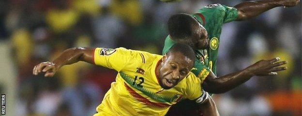 "Mali""s Seydou Keita (left) and Franck Kom of Cameroon challenge for the ball"