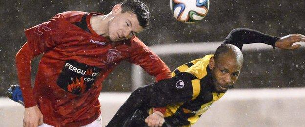 Larne's Stuart McMullan beats Miguel Chines of Carrick to the ball during the Irish Cup match