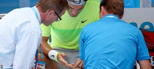Roger Federer inspects his hand in his match against Simone Bolelli