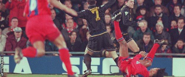 Eric Cantona holds his arms aloft as Crystal Place defender Richard Shaw falls to the ground