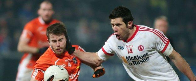 Michael Murray is challenged by Red Hands forward Sean Cavanagh at the Athletic Grounds