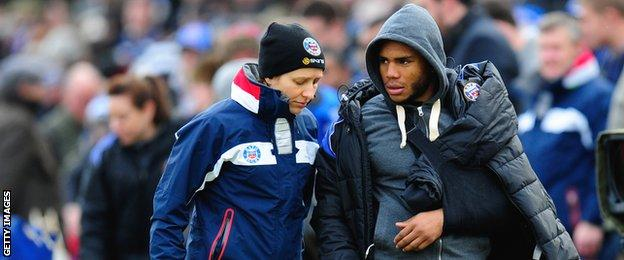 Bath's England centre Kyle Eastmond is led away with his arm in a sling