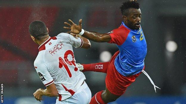 Tunisia forward Ahmed Akaichi (left) jumps to head the ball with DR Congo defender Issama Mpeko