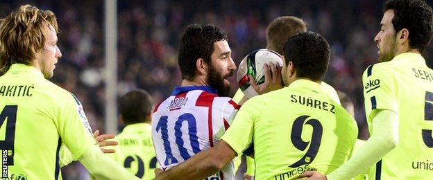 Arda Turan is led away by Barcelona players