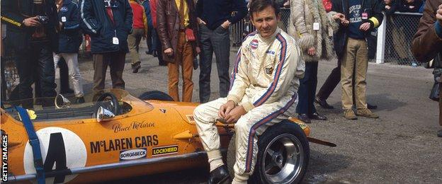 Bruce McLaren sits on a wheel of the M14A in 1970