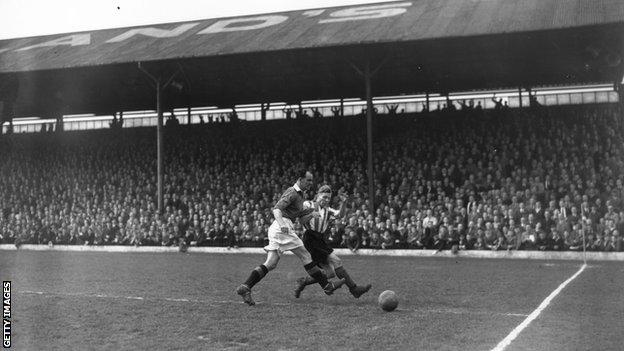 Manchester United's Jack Carey tackles a Brentford player during a match at Griffin Park in April 1947