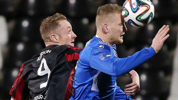 Crusaders forward Timmy Adamson is beaten to the high ball by Dungannon's David Armstrong