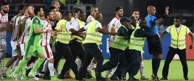 Security guards protect referee Rajindraparsad Seechurn from Tunisia's players