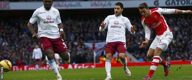 Mesut Ozil (right) scores for Arsenal