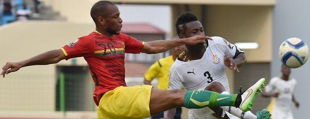 Guinea defender Baissama Sankoh (left) challenges Ghana forward Asamoah Gyan