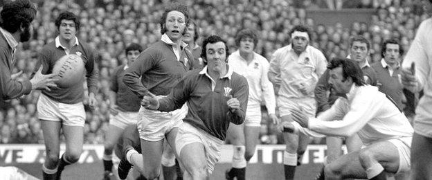 Wales' Phil Bennett sends out a pass against England in 1976, as JPR Williams looks on