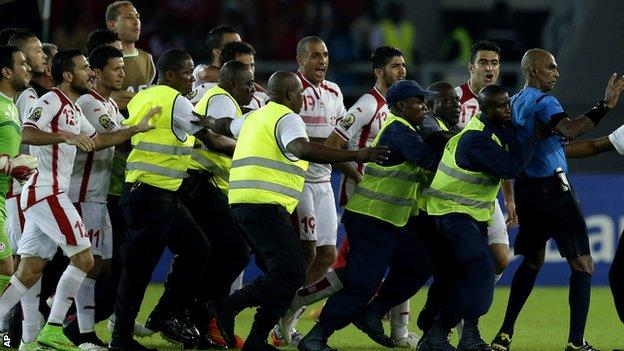 Referee Rajindraparsad Seechurn is confronted by Tunisia players after the game against Equatorial Guinea